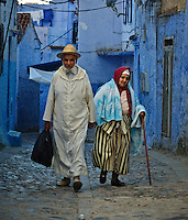 Elderly couple walking hand in hand through the beautiful blue city of Chefchaouen wearing their traditional gowns