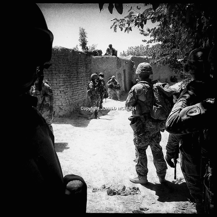 US troops from 1-38 Infantry plan their next move moments after a Taliban fighter jumped up from behind a wall and started shooting at them from about 20 feet away in Pay-E Moluk village in Panjwayi, Kandahar, 30 April 2013. The patrol was ambushed and turned into a five hour firefight. (John D McHugh)