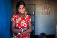 Nitu (not her real name), stands at the doorway at her home in Jhaju village, Bikaner, Rajasthan, India on 4th October 2012. Now 18, she was married off at age 10 to a boy of around the same age, but only went to live with her in-laws when she was 12, after she had finished studying up to class 6. The three sisters, aged 10, 12, and 15 were married off on the same day by their maternal grandfather while their father was hospitalized. She was abused by her young husband and in-laws so her father took her back after hearing that her husband, who works in a brick kiln, was an alcoholic and was doing drugs and crime. She had only spent a few days at her husband's house at that time. Her father (now out of the hospital) has said that she will only be allowed to return to her husband's house if he changes his ways but so far, the negotiations are still underway. Photo by Suzanne Lee for PLAN UK