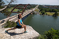 Young slim lady doing stretching exercises on a cliff overlooking the 360 Bridge and Lake Austin on a beautiful summer's day.