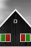 An alternative triangular gable of a Dutch house with colorful shutters.