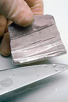 SODIUM METAL CUT WITH KNIFE<br /> Highly Reactive Alkali Metal<br /> Sodium metal has a silvery appearance when freshly cut but quickly tarnishes as it is exposed to air. Due to its highly reactive properties, sodium metal is stored in oil.