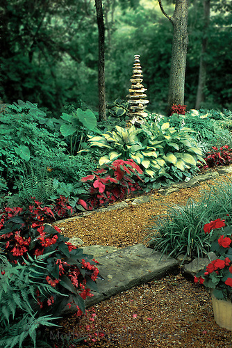 Tall Cairn in shade garden made of river rock surrounded by hostas, begonias, ferns, and impatience blooms