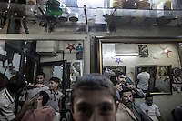 At the evening time a group of man await for their turn as another ones get different services at one of the numerous barber shops in downtown Manbij, located at the northeast of Aleppo province.