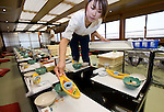 """A staffer sets the tables in readiness for an evening of entertainment aboard a """"Yakata-bune"""" pleasure boat run by the Harumiya Co. in Tokyo, Japan on 31 August  2010. Photographer: Robert Gilhooly"""