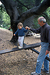 Berkeley, CA Grandfather giving support to granddaughter's experimentation on teeter totter in public park.  Child two years old  MR