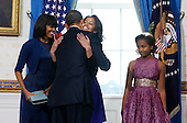 United States President Barack Obama gets a hug from his daughter Malia as wife Michelle (L) and daughter Sasha (R)  looks on in the Blue Room of the White House in Washington, January 20, 2013. .Credit: Larry Downing / Pool via CNP
