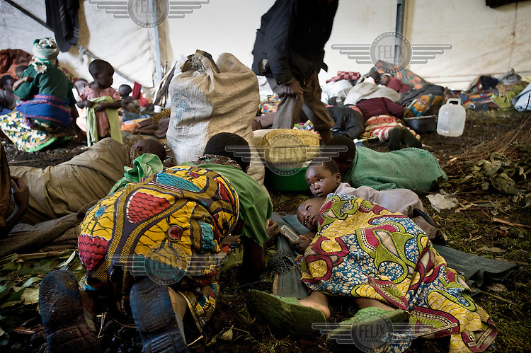 Displaced people who have fled renewed fighting in the region take shelter as fighting erupts within the Kibati camp. Government troops fired a number of rounds.
