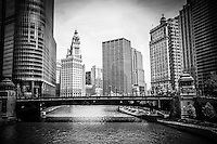 Black and white Chicago skyline along the  Chicago River at Wabash Avenue bridge with the Wrigley Building and other downtown city buildings during the day.
