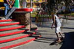 A young couple holds hands in the Sayulita, Mexico town square as a skateboarder passes. A popular destination for surfers and sport fisherman, Sayulita is a short drive north of Puerto Vallarta.