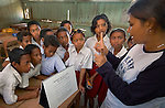 Hesti Widodo, RARE Pride Campaign Manager, gives a lesson on coral reefs at a schoolhouse in Komodo Village, Komodo National Park