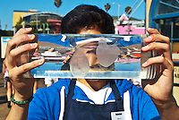 Heal the Bay Volunteer Shou Kaida shows off a moon jelly at the Santa Monica Pier while promoting Santa Monica Pier Aquarium's Ocean Appreciation Celebration this weekend, July 28th & 29th from 12:30-6:00PM. .