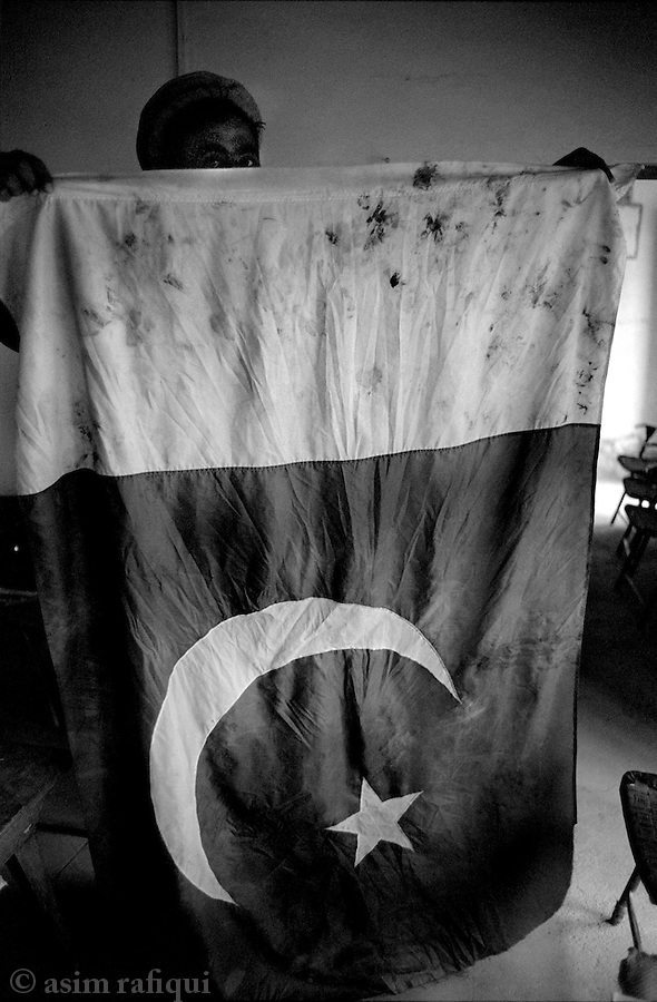 dezaghundai, waziristan, april 2004: a man holds up a pakistani flag that he claims was used by pakistani soldiers as a footmat when they had forcibly occupied the premises.  the local high school where this incident took place had earlier been hit my missle fire from a pakistan army helicopter.   the actions were part of pakistan's campaign to capture al qaeda fighters suspected of hiding out in remote parts of waziristan<br />