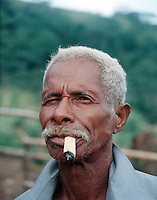 March 2nd 2004 Luro, East Timor-A man smokes a cigarette hand rolled in corn husk in the remote town of Luro, which is located in the Lautem District of East Timor.  Daniel J. Groshong/Tayo Photo Group.