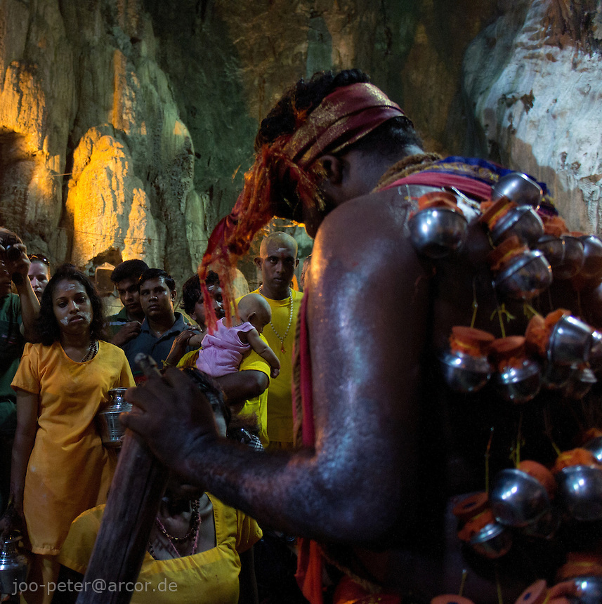 man in trance giving blessings  while Thaipusam ceremonies inside Batu Caves, Kuala Lumpur, Malaysia, 2012. Thaipusam ceremonies, celebrated by tamile Hindu community in Malaysia, take place  in Sanctuary of Batu Caves at the border of Kuala Lumpur, each year around end of January or beginning of February, according to Hindu moon calendar. The event is paying hommage to Lord Murugan, a spirit or god created by Shiva to lead the army of gods against the army of evil demons, finally defeating the evil spirits. There are many ways to present offerings or sacrifices for this major religious event. Devotees mortify their bodies by carrying heavy kavaris with spears fixed in their skin or fruits, flowers and little post with holy milk fixed with hooks in their skin, ascending the stairways to the sanctuary in trance, `followed by assistant  taking care and musicians playing loud and fast rhythmic trance music.  Many families shave their head in a ritual before ascending the stairways, as part of rituals to obtain salvation for their ancestors.
