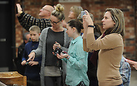 NWA Democrat-Gazette/ANDY SHUPE<br /> Members of the St. Joseph Catholic Church in Tontitown take photographs of Items used by Donald Nohs, director general of the Confraternity of the Passion International, in his presentation about the Should of Turin Saturday, Jan. 16, 2016, at the church.