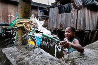 A Colombian girl fills plastic barrels with safe drinking water inside the stilt house area in Tumaco, Colombia, 17 June 2010. Although Latin America (as a whole) is blessed with an abundance of fresh water, having 20% of global water resources in the the Amazon Basin and the highest annual rainfall of any region in the world, an estimated 50-70 million Latin Americans (one-tenth of the continent's population) lack access to safe water and 100 million people have no access to any safe sanitation. Complicated geographical conditions (mainly on the Pacific coast), unregulated industrialization (causing environmental pollution) and massive urban poverty, combined with deep social inequality, have caused a severe water supply shortage in many Latin American regions.