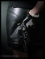 Girl with her handgun, leather and pearls