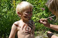 Kind, Junge wird mit Erdfarben bemalt, Körperbemalung, Kinder malen mit selbstangemischten Erdfarben, Farbe aus verschiedenfarbiger Erde,