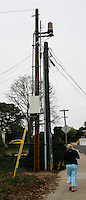 A wonan walks beneath a cell phone antenna (cylinder, upper center)  mounted on a sepearte utility pole behind an existing one near the Intersection of Catalina Boulevard and Naragansett in Ocean Beach, January 3, 2008.  At least one neighbor near the site was unaware of what the antenna was.