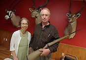 Sandy and John Krieger, owner of Krieger Barrels, pose with a rifle that is made with one of their products in a conference room at the Richfield plant on Thursday, Sept. 24, 2009. On the wall are mounted trophy heads from John Krieger's African hunting trips. Ernie Mastroianni photo.