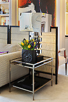 A metal side table beside the sofa in the living room holds one of a pair of metal lamps and a vase of tulips