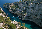Several sailboats float in a calanque between rocky cliffs, Provence, France