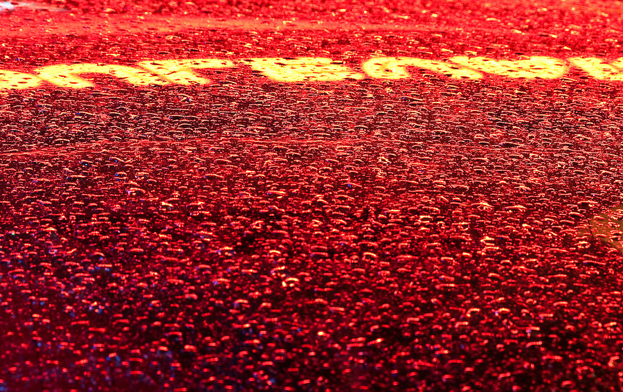 Close up of drops and sign reflection on a glass after raining in Miami Beach