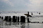 Man holding surfboard heads into water to surf and waits to catch a wave.