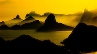 Overview of the mountains of Rio de Janeiro and entrance of Guanabara Bay at sunset with Sugar Loaf Mountain in the center, Morro Dois Irmaos (Two Brothers Mountain) to the left, Rock of Gavea in the mid-left at background and Corcovado Mountain with Christ the Redeemer Statue atop of it at right, Brazil.
