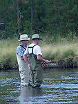 A senior citizen shows a younger man how to fly fish.