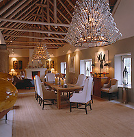 A long barn-like living/dining room is decorated with a pair of giant chandeliers made from wine bottles of clear glass