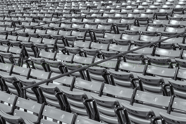 """Empty grandstand seats in Fenway Park wait for the next home game to be filled with fans of the """"Red Sox Nation"""".  Fenway is the oldest ballpark in Major League Baseball, dating from 1912."""