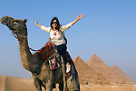 Woman on camel back visiting the Pyramids in Giza at Cairo, Egypt
