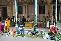 Women sell flowers and herbs for temple offerings by The Golden Temple during Festival of Shivaratri in holy city of Varanasi, India