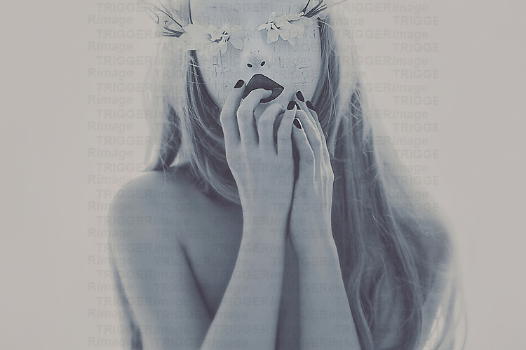 Female youth with long blonde hair  with hands touching lips and wearing a mask made of flowers looking at camera