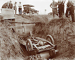 Vintage Photo: Overturned Auto being removed from a ditch after an accident 1926. Car crash with spectators looking on.