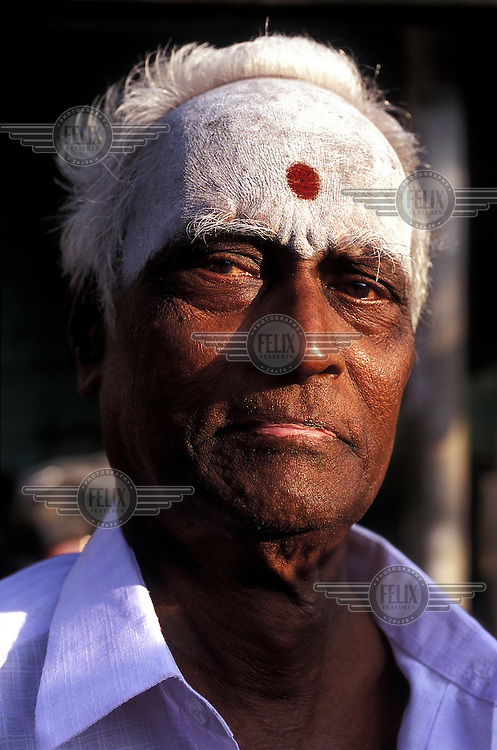 A man with his forehead painted using a white paste made from newly harvested rice, celebrating Pongal, the Tamil New Year.