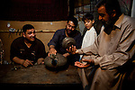 NAJAF, IRAQ: A metalsmith negotiates a price with a customer in the Najaf market...Daily life continues in relative peace in the Iraqi city of Najaf...Photo by Ali Arkady/Metrography