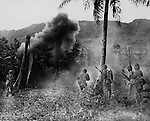 "Marines attacking a Japanese position on Saipan flush the enemy out with a demolition charge and pick them off with rifles as they attempt to escape. ""At the instant this picture was made, the Leathernecks had just shot a Son of Heaven as he came out of his foxhole."""