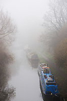Narrowboats - skinny, barge-like boats used as houseboats on Britain's narrow waterways - disappear into the mist on a foggy morning on the Oxford Canal.