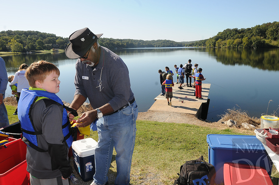 NWA Democrat-Gazette/FLIP PUTTHOFF <br /> Wilson &quot;Scotty&quot; Scott Jr., helps students don life jackets Sept. 30 2016 which they wear while fishing.