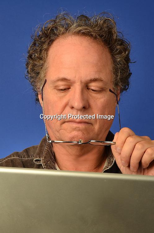 Old man on computer stock photo