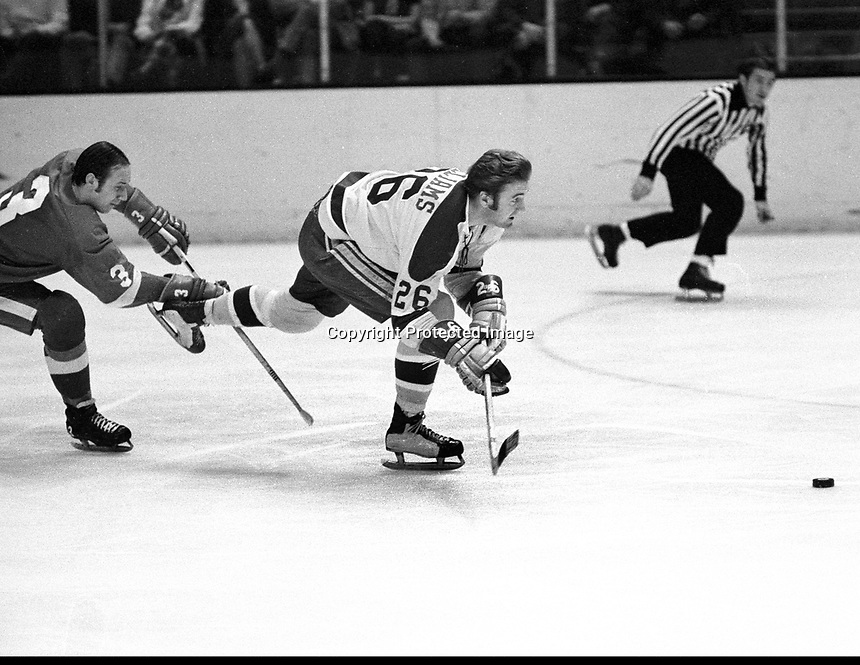 Seals Tommy  Williams chases puck against the RedWings, chased by #3Dale Rolfe. (photo by Ron Riesterer)