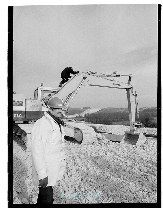 A protester climbs onto earth moving machinery to disable it  on the  M3 extension Winchester . Twyford down..Group4 security watch on