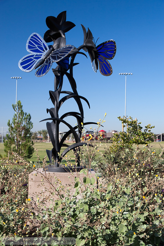 The butterfly statue at Stanton Central Park, seen on a clear sunny day with the iconic train play structure and baseball field lights visible in the background, along with some of the plantings visible in the front.  The statue is made of blue glass, stainless steel, and black iron.