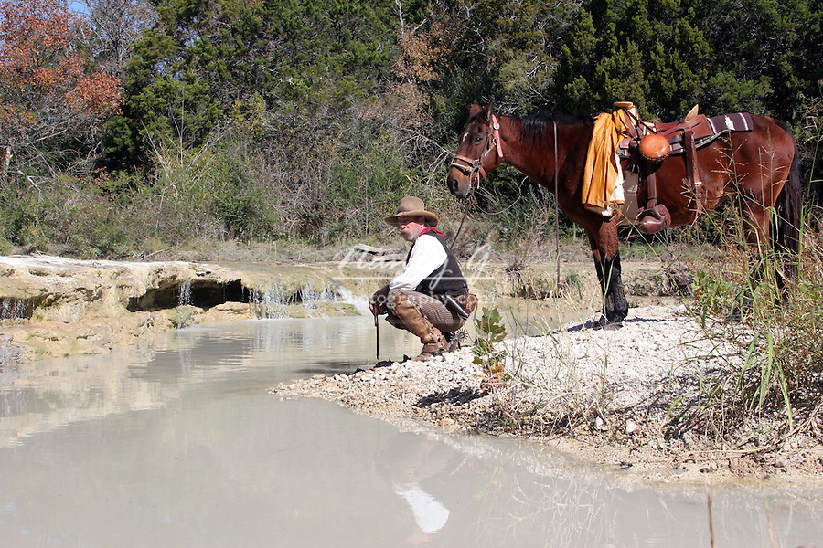 A cowboy and horse resting by a stream in the old West