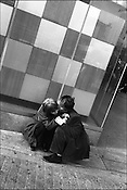 Young courting couple kissing as they squat on the ground outside Starbucks in Shibuya district, Tokyo, Japan