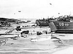 In this photo provided by the Office of War Information, U.S. landing crafts are beached on the Normandy shore to unload troops and supplies to back up Allied advances against the Nazis in France, June 6, 1944. (AP Photo/Office of War Information)