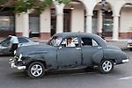 Havana, Cuba; a classic gray 1952 Chevy driving along the Paseo de Marti past the Saratoga Hotel
